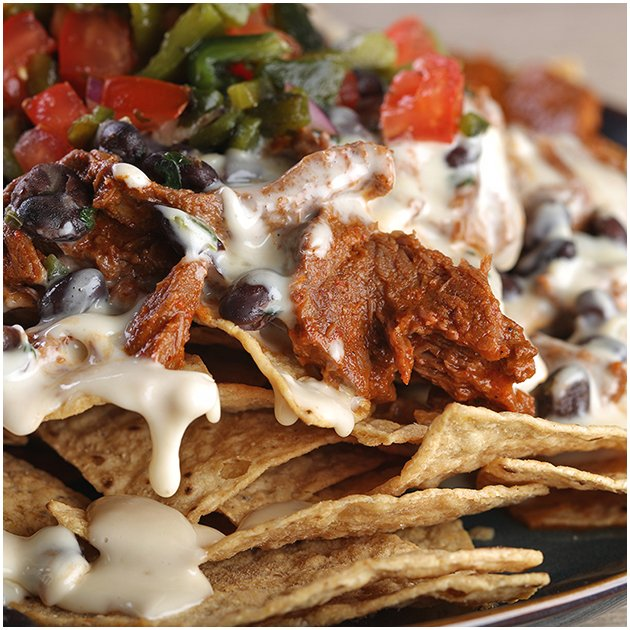 Close up of nachos with cheese sauce, pulled meat, and beans