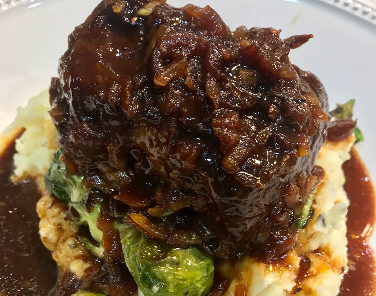 Cranberry-braised beef ribs on a bed of mashed potatoes and Brussel sprouts